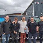 Five men stood in front of a black van